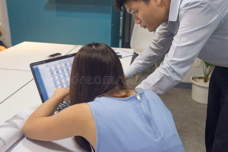 Employé asiatique d'affaires discuter au sujet des données financières sur l'ordinateur portable images libres de droits