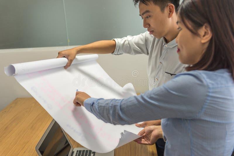 Employé asiatique d'affaires discuter avec le collègue au sujet du dessin photographie stock libre de droits