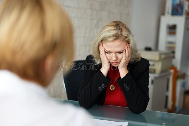 Employé blond déprimé écarté dans le bureau photos stock