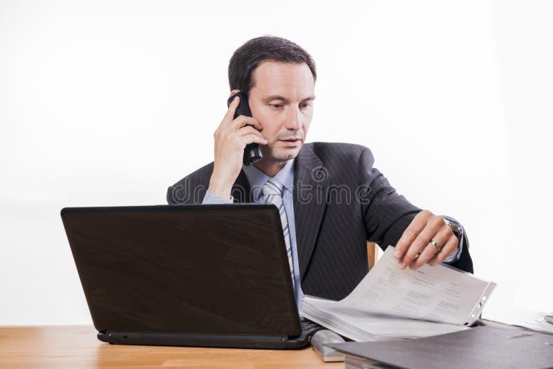 Employé commis vérifiant des dossiers au téléphone photographie stock