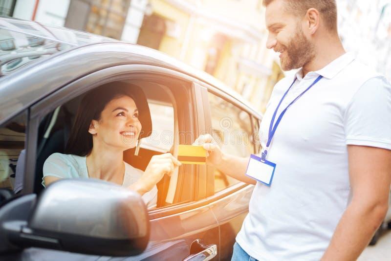 Employé d'agence de location de voiture recevant une carte de crédit images stock