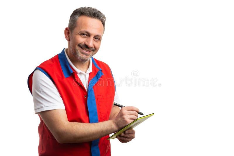 Employé d'hypermarché prenant des notes sur le comprimé photo libre de droits