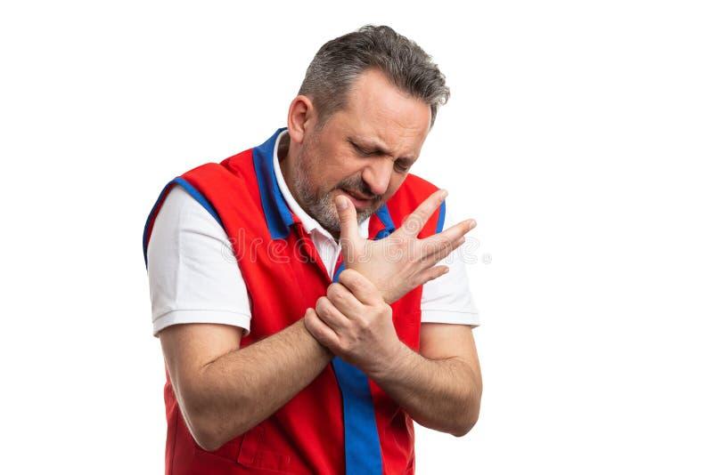 Employé d'hypermarché tenant le poignet foulé image libre de droits