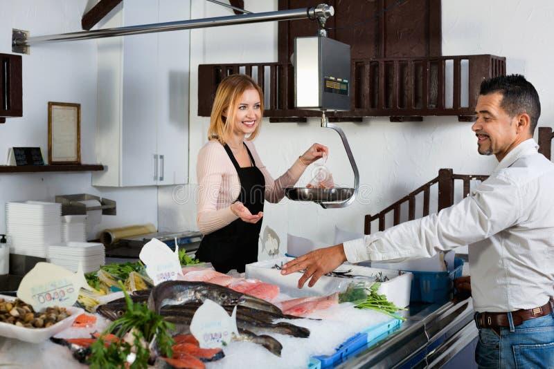 Employé de boutique souriant vendant le poisson frais et les fruits de mer effrayants image libre de droits