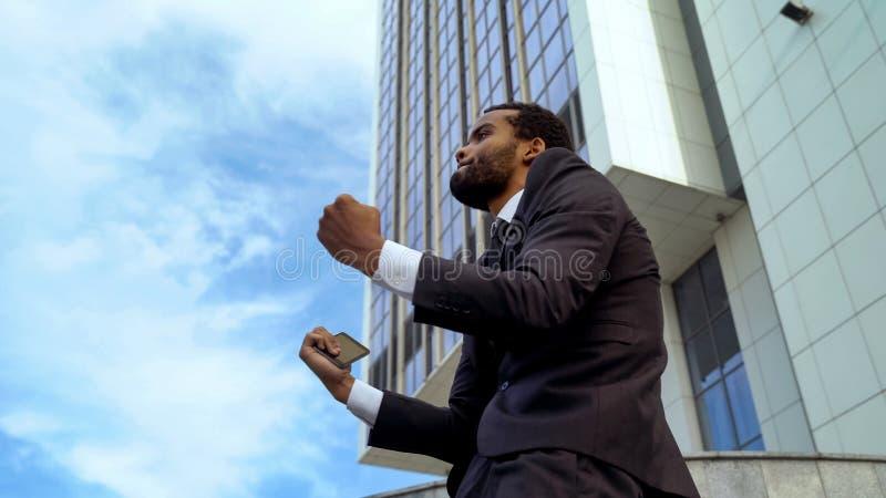 Employé de bureau afro-américain heureux au sujet de bonnes nouvelles, promotion, démarrage réussi images libres de droits