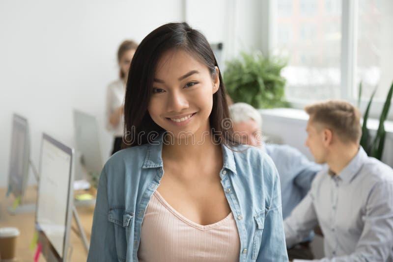 Employé de bureau asiatique de sourire regardant l'appareil-photo fonctionnant avec le col images libres de droits