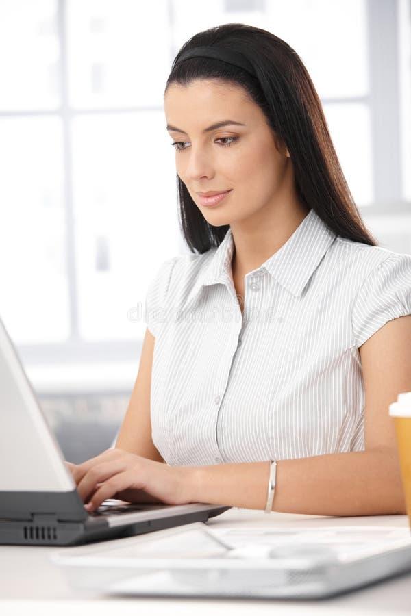 Employé de bureau avec l'ordinateur portatif image stock