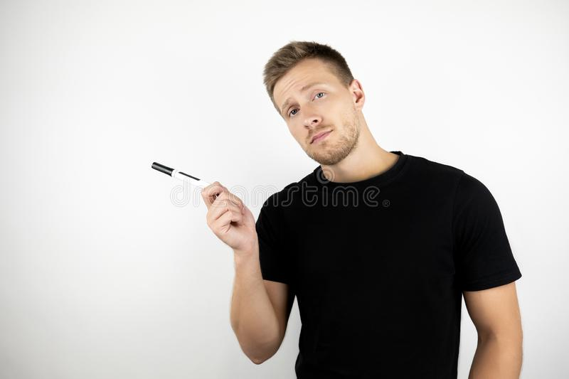 Employé de bureau bel de jeune homme portant le marqueur noir de participation de T-shirt pour des notes écrivant le fond blanc d image libre de droits