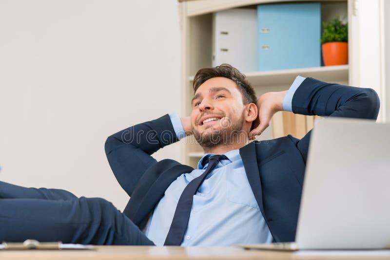 Employé de bureau comblé s'asseyant à la table photo libre de droits