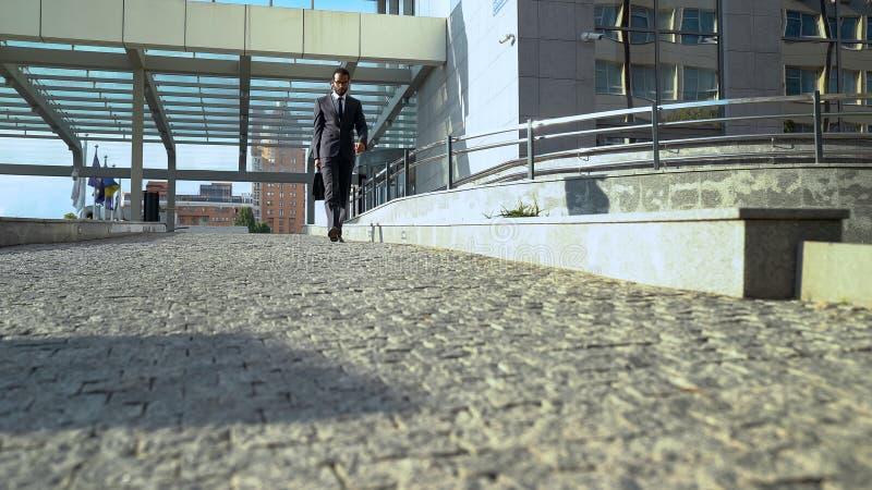 Employé de bureau dans le formalwear laissant le centre d'affaires à la fin du jour ouvrable photographie stock libre de droits
