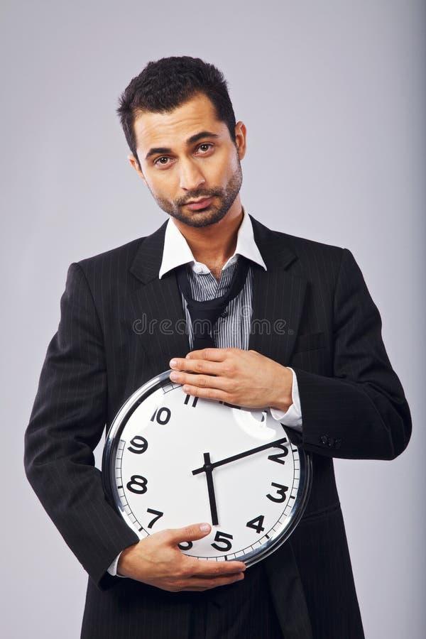Employé de bureau de sexe masculin avec une horloge murale photo stock
