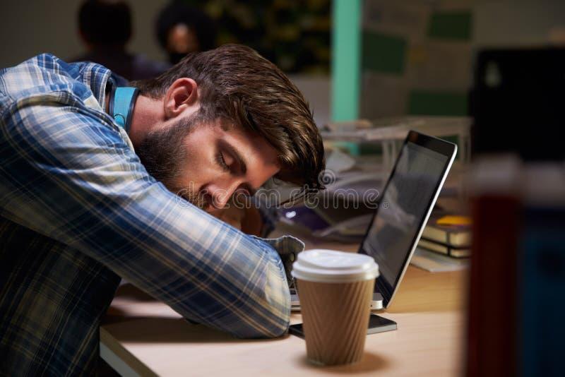 Employé de bureau de sexe masculin endormi au bureau travaillant tard sur l'ordinateur portable photo stock