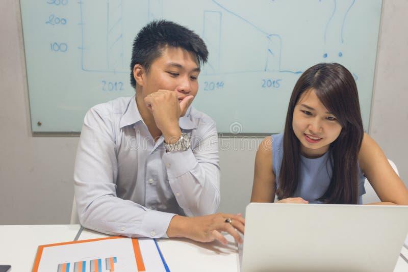 Employé de bureau discuter au sujet du nombre financier sur l'ordinateur portable photos stock