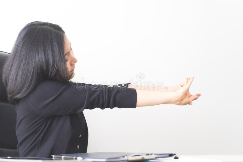 Employé de bureau féminin asiatique étirant le bras dans le bureau photographie stock libre de droits