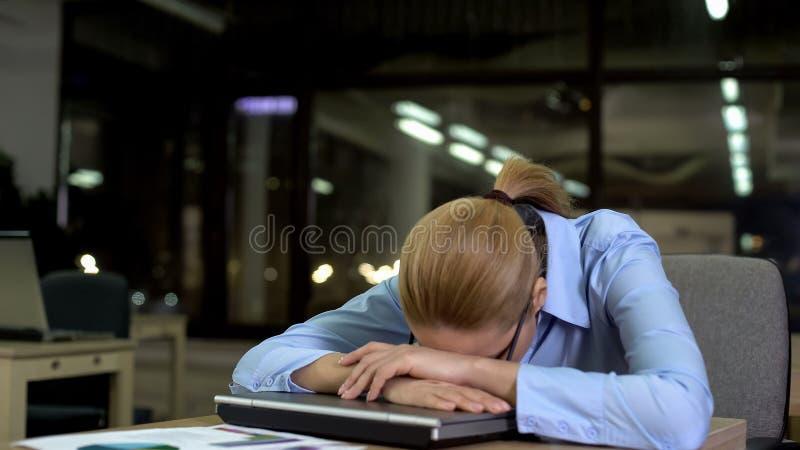 Employé de bureau fatigué se trouvant sur l'ordinateur portable, le concept de la routine quotidienne et le surmenage images stock