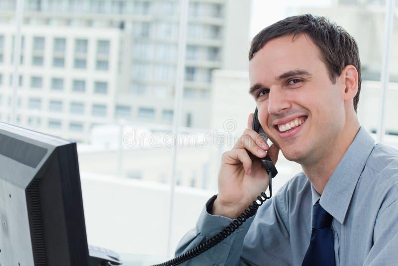 Employé de bureau heureux au téléphone photos stock