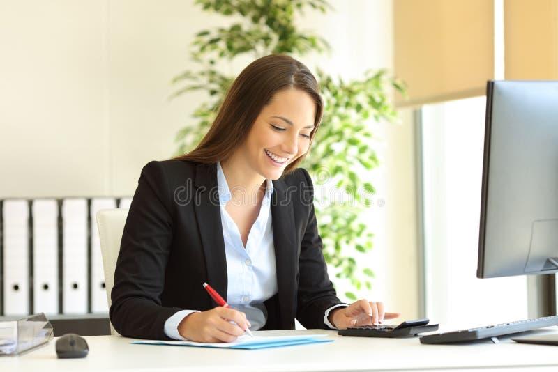 Employé de bureau heureux calculateur et écrivant le budget image stock