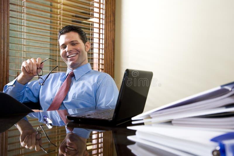 Employé de bureau heureux travaillant sur l'ordinateur portable photo stock