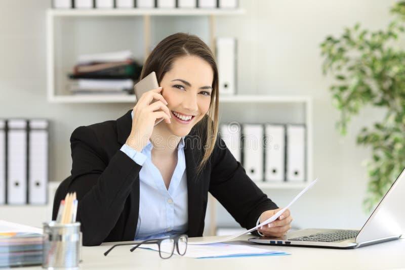 Employé de bureau invitant le téléphone vous regardant photo stock