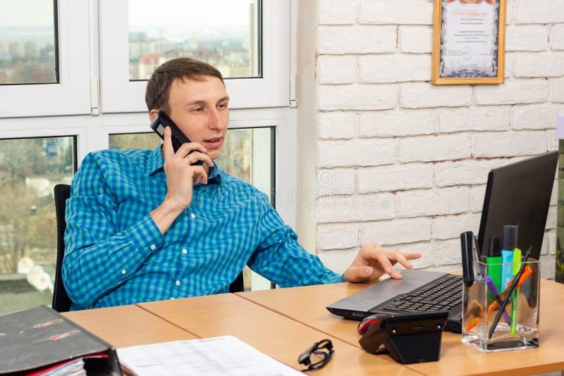 Employé de bureau parlant au téléphone et travaillant dans un ordinateur portable photographie stock libre de droits