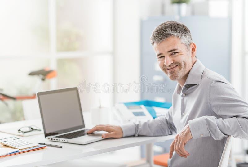 Employé de bureau sûr s'asseyant au bureau et travaillant avec un ordinateur portable, il sourit à l'appareil-photo photographie stock