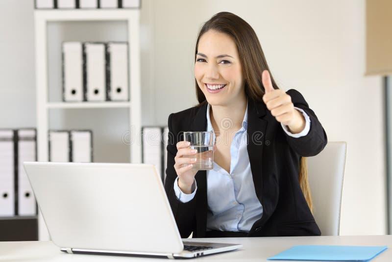 Employé de bureau tenant un verre de l'eau vous regardant photos libres de droits