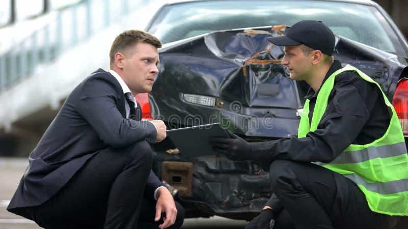 Employé de la compagnie d'assurances tenant une tablette montrant le conducteur masculin sur les lieux de la collision photo stock