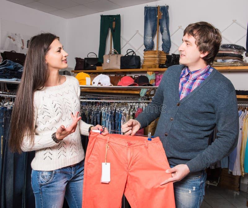 Employé de magasin montrant des jeans photographie stock libre de droits