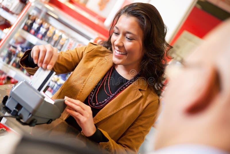 Employé de magasin souriant tout en calottant par la carte de crédit image libre de droits