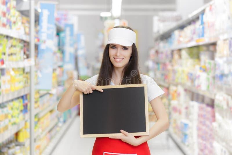 Employé de sourire de supermarché tenant un tableau noir vide image libre de droits