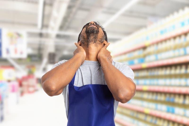 Employé de supermarché étirant le cou douloureux photo stock