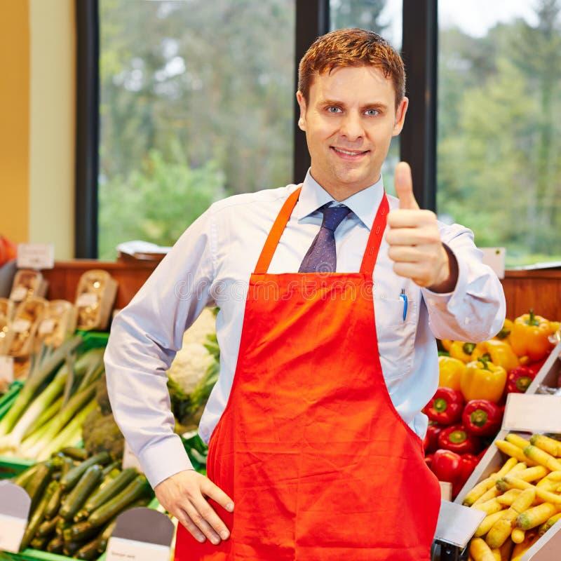 Employé de supermarché tenant des pouces  images stock