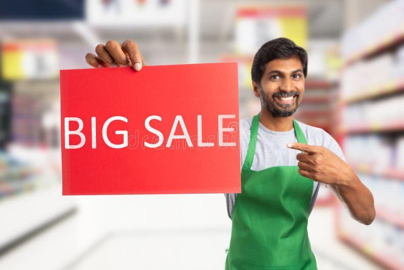 Employé de supermarché tenant le grand papier de vente photographie stock libre de droits
