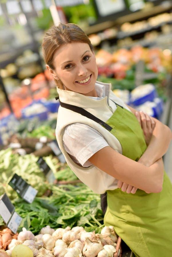Employé de supermarché vendant les légumes frais images libres de droits