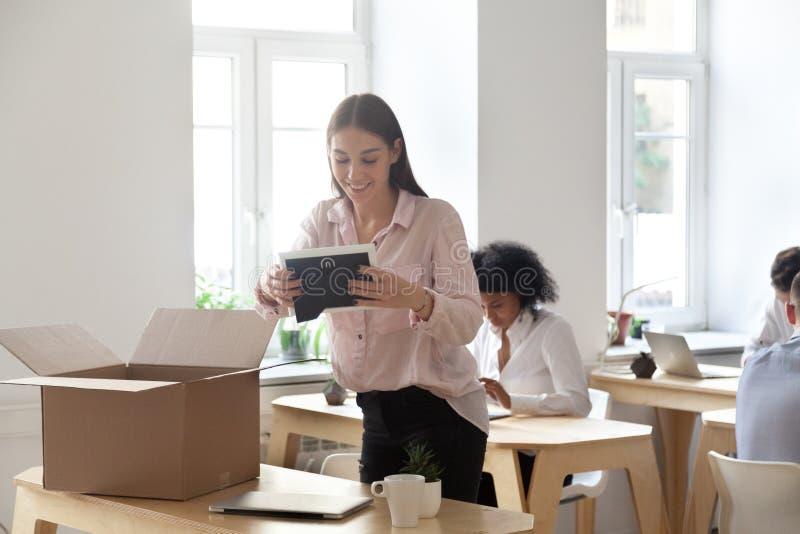 Employé féminin enthousiaste déballant le premier jour ouvrable photo libre de droits