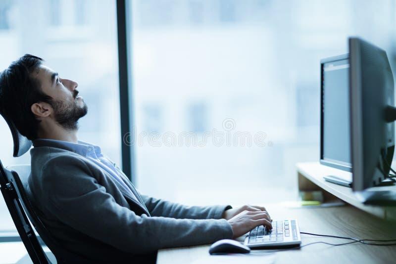 Employé fatigué surchargé sur le lieu de travail dans le bureau étant malheureux image libre de droits