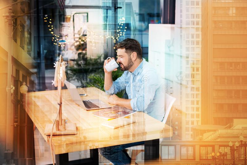 Employé qualifié se sentant heureux tout en buvant du café et travaillant à la maison photos libres de droits