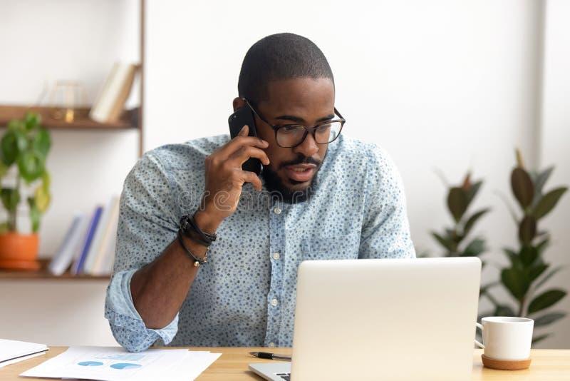 Employ? s?rieux d'afro-am?ricain faisant l'appel d'affaires concentr? sur l'?cran d'ordinateur portable photos stock