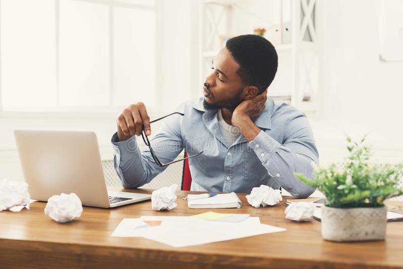 Employé se surmenant d'afro-américain sur le lieu de travail photographie stock libre de droits