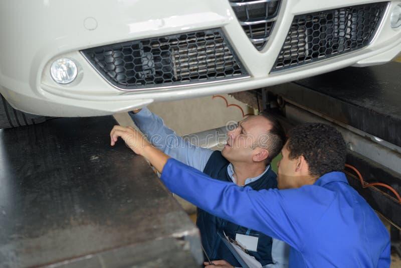 Employés d'atelier travaillant ensemble sous la voiture soulevée photographie stock libre de droits