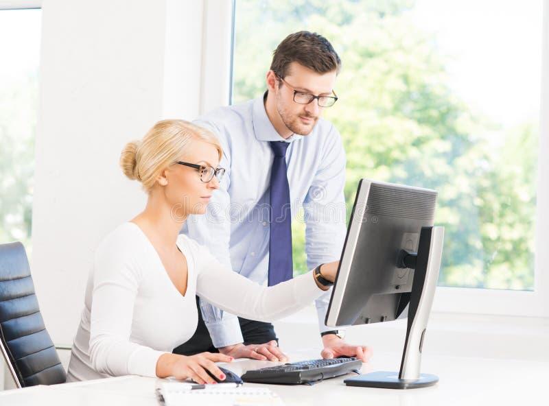 Employés de bureau dans le formalwear fonctionnant dans le bureau images libres de droits