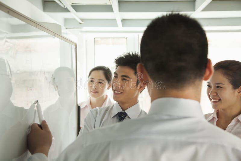 Employés de bureau de sourire regardant le diagramme sur le tableau blanc et le pointage photographie stock libre de droits