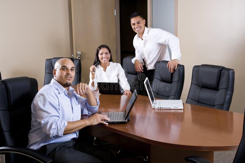 employés de bureau hispaniques de Mi-adulte dans la salle de réunion images stock