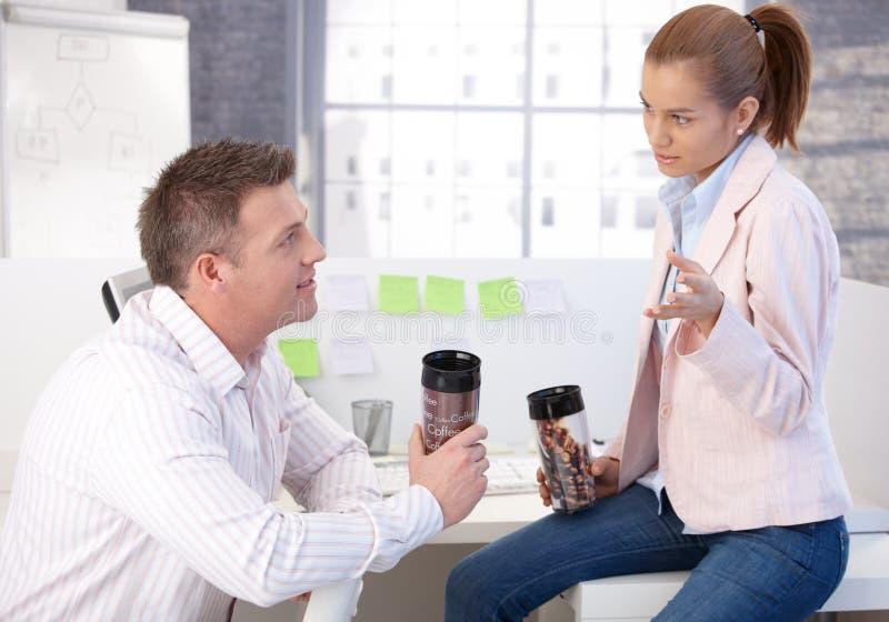 Employés de bureau occasionnels ayant la causerie de pause-café image stock