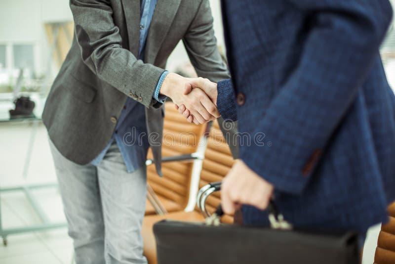 Employés de la société avec des serviettes se serrant la main dans le lobby d'un bureau moderne images libres de droits