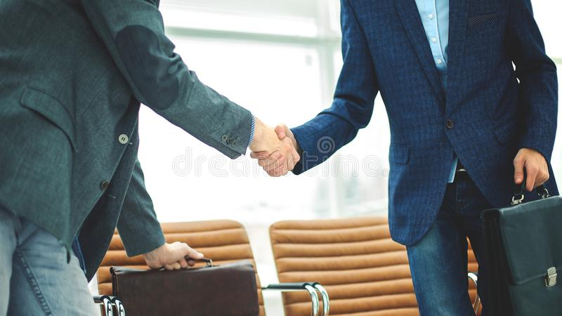 Employés de la société avec des serviettes se serrant la main dans le lobby d'un bureau moderne images stock