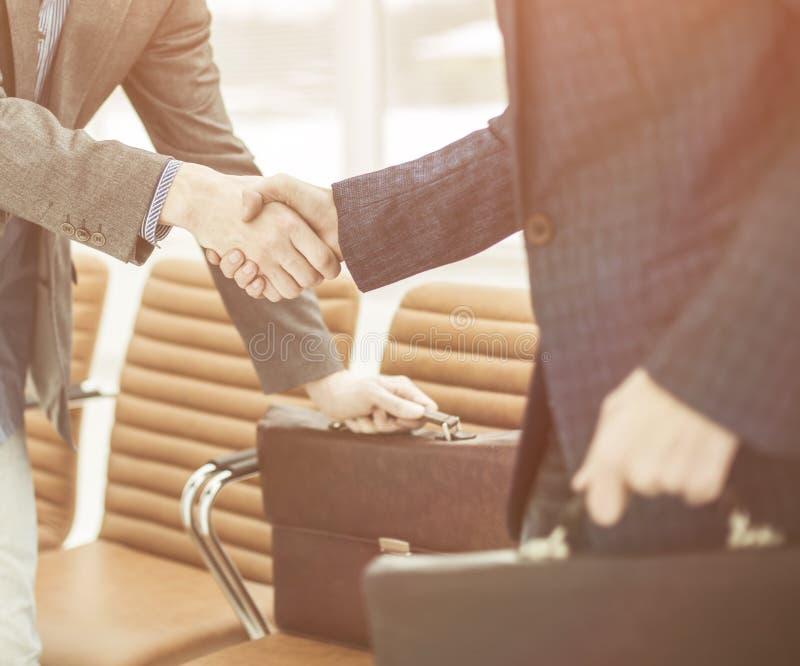 Employés de la société avec des serviettes se serrant la main dans le lobby d'un bureau moderne photographie stock