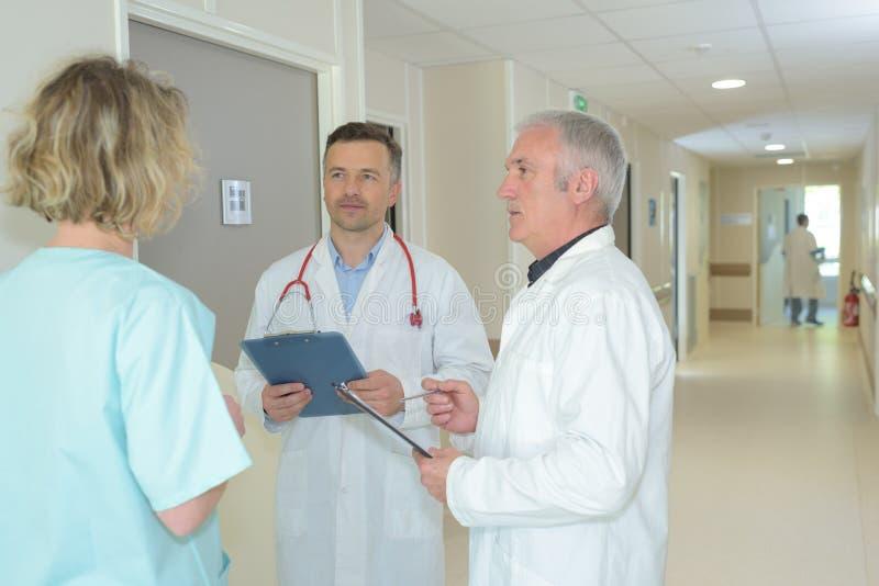 Employés de santé de groupe discutant dans le couloir d'hôpitaux images libres de droits
