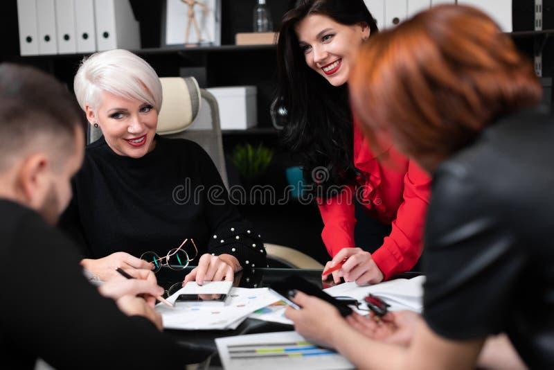 Employés de sourire parlant dans le lieu de travail image libre de droits