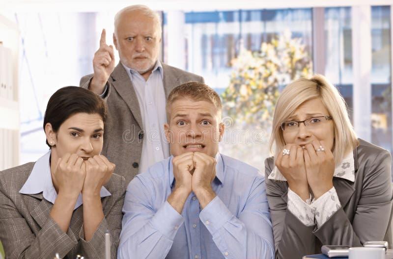Employés effrayés s'asseyant avec le bossage fâché derrière photo libre de droits